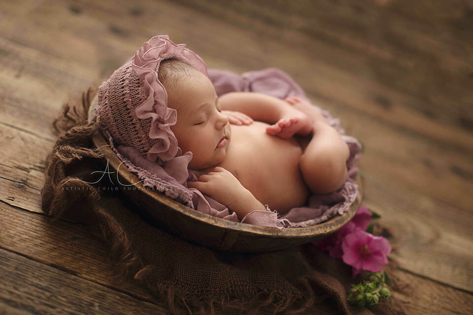 South East London Newborn Baby Girl Portraits | backlit side portrait of a newborn baby girl sleeping in a wooden bowl during her newborn photo session