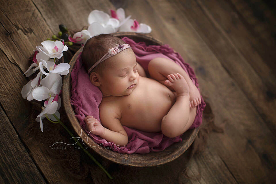 South East London Newborn Baby Girl Portraits | newborn baby girl sleeping peacefully in a wooden bowl surrounded by white flowers