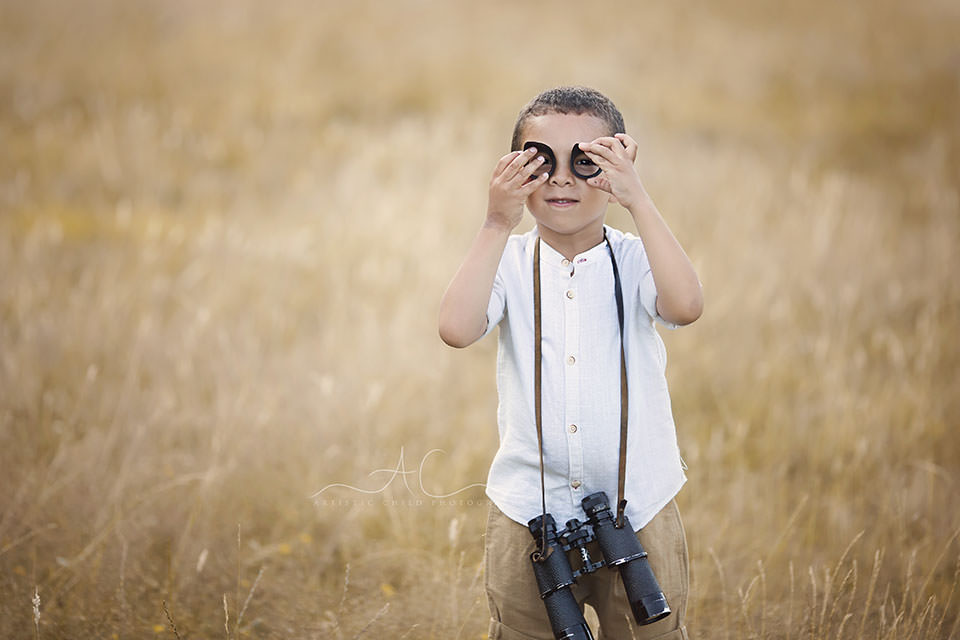portrait of a 5 year old boy holding binoculars while playing in the park | London