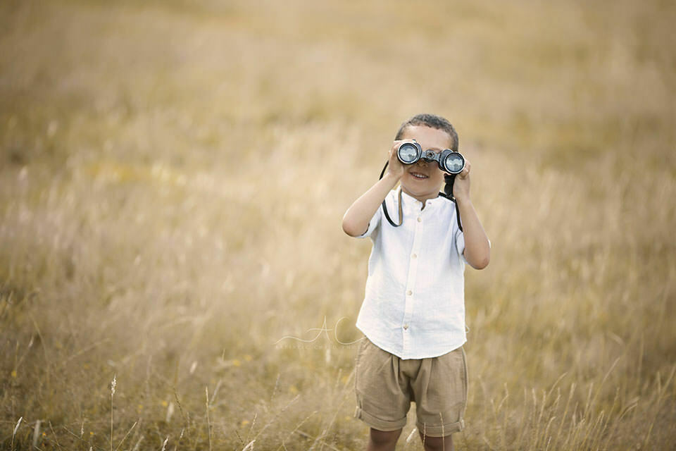portrait of a 5 year old boy playing with binoculars in the park | London
