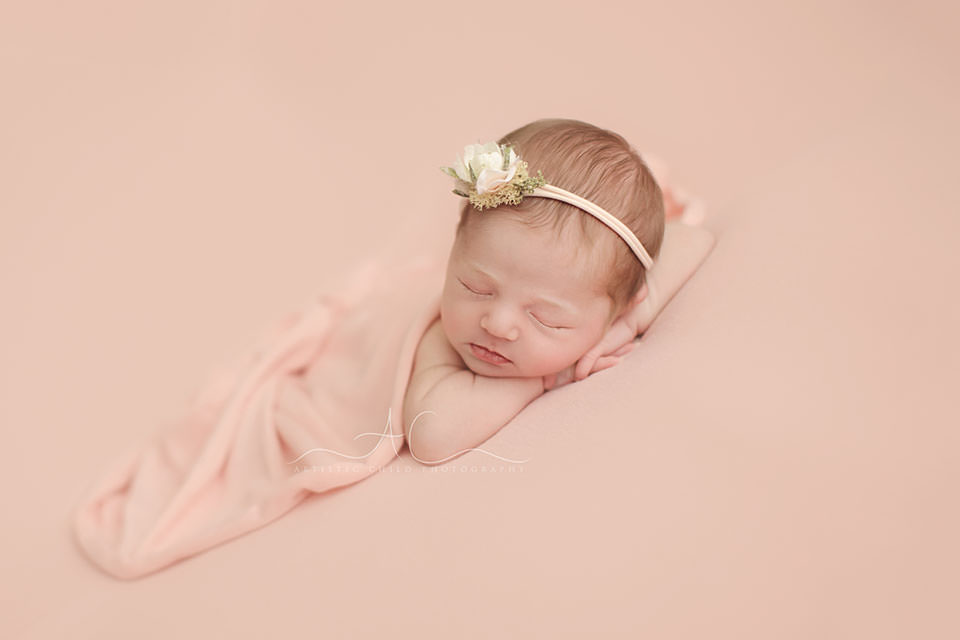 newborn baby girl photographed in hands under chin pose   London