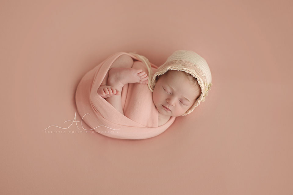 portrait of a newborn baby girl swaddled in a pink wrap   London