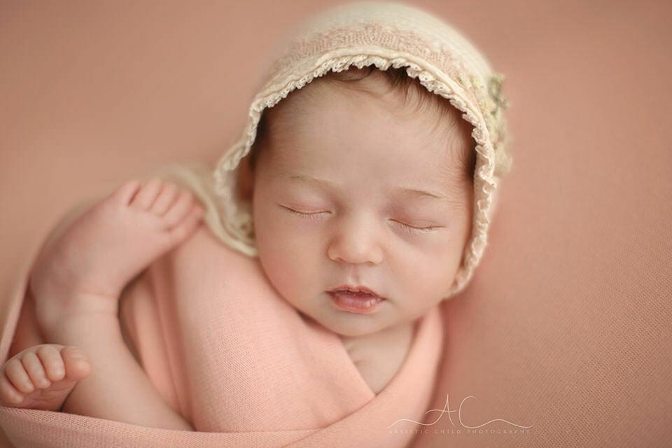 a close up portrait of a newborn baby girl wearing a pink bonnet   London