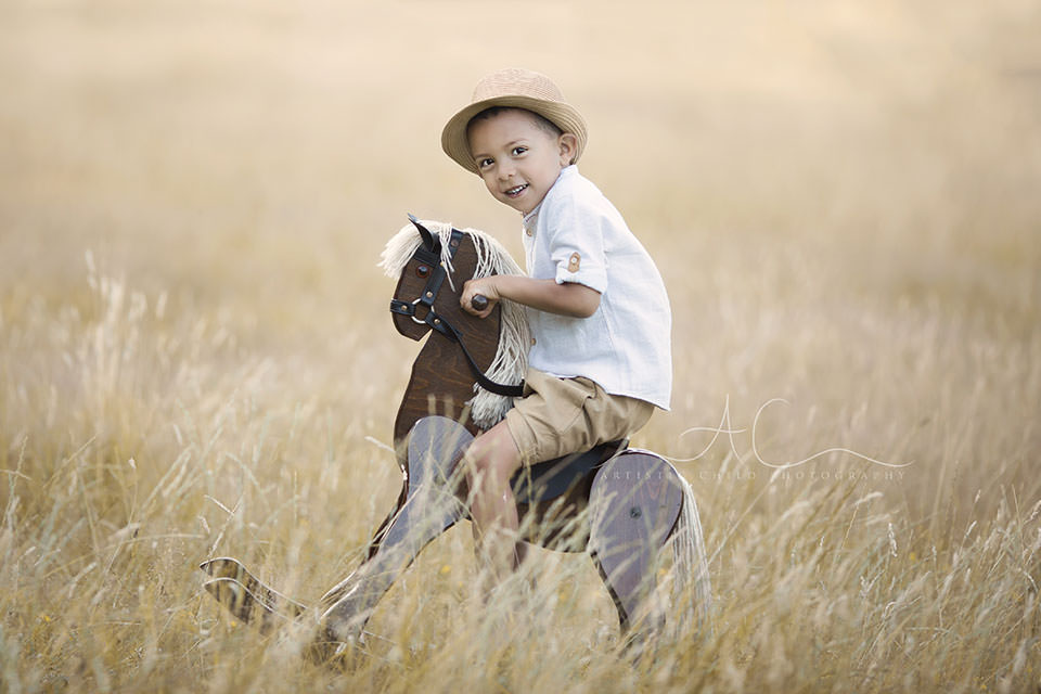 London Children Photography Services | portrait of a 5 year old boy sitting on a rocking hors and wearing a straw hat