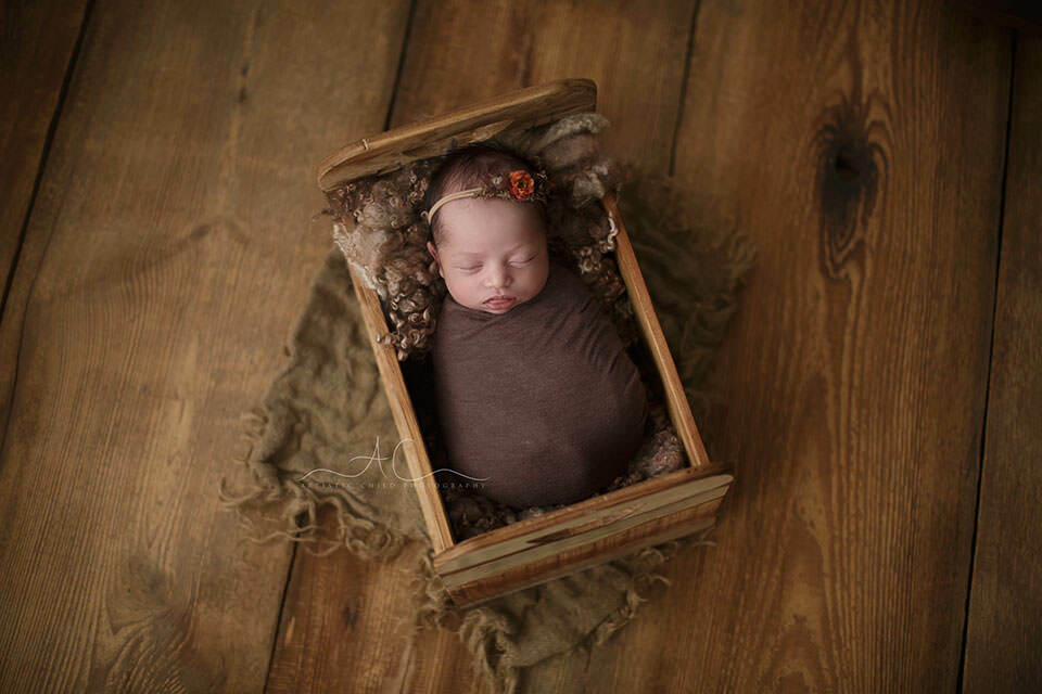 photo of a newborn baby girl in a wooden bed prop | London