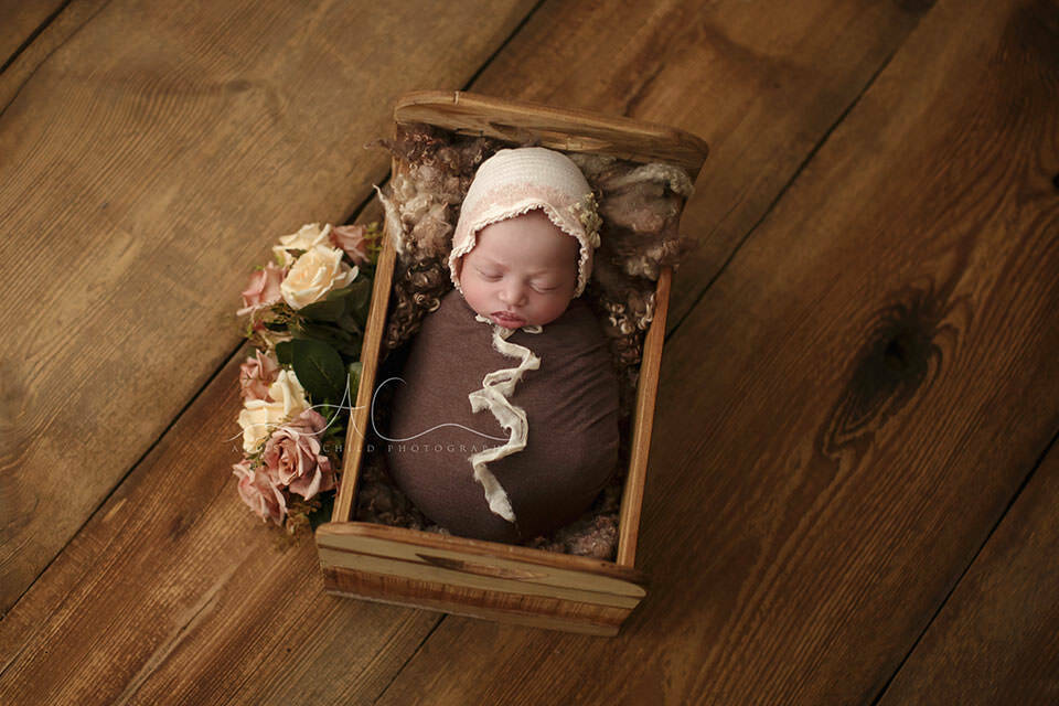 photo of a newborn baby girl sleeping in a wooden bed surrounded by flowers | London