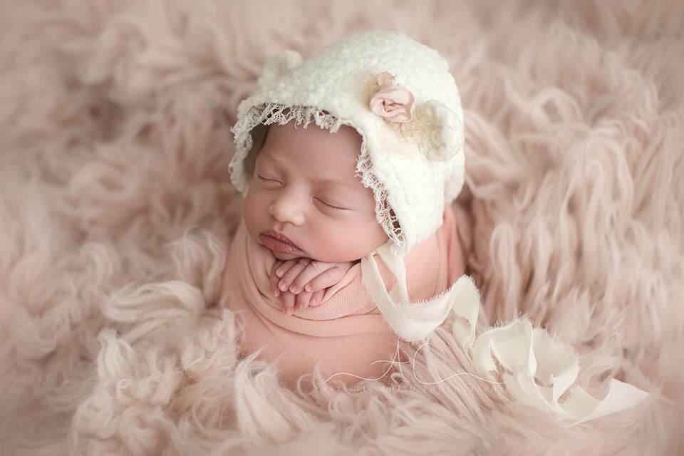 newborn baby girl posed in a potato sack pose on pink flokati | London