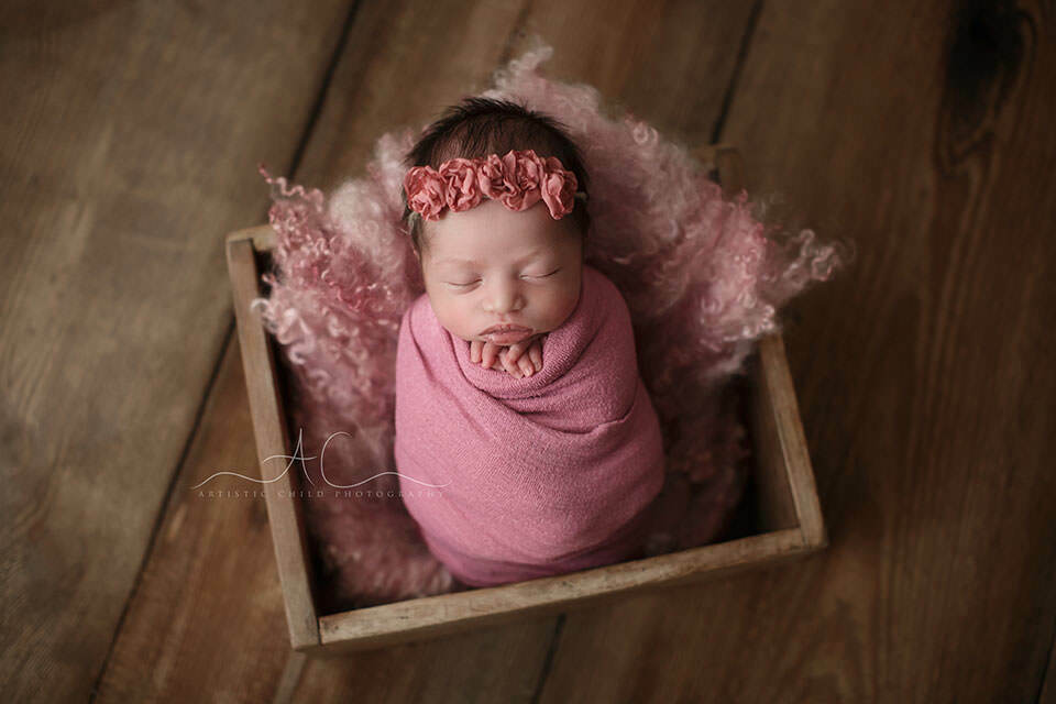 newborn baby girl photographed in a wooden crate while sleeping swaddled in a pink wrap | London