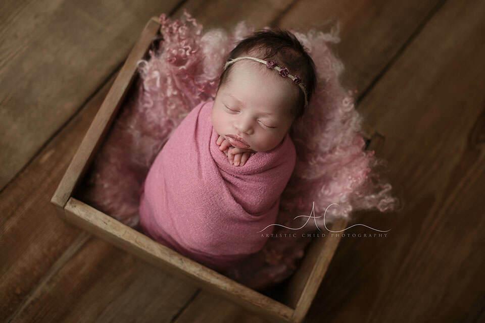 portrait of a newborn baby girl wearing a beautiful flower hairband | London