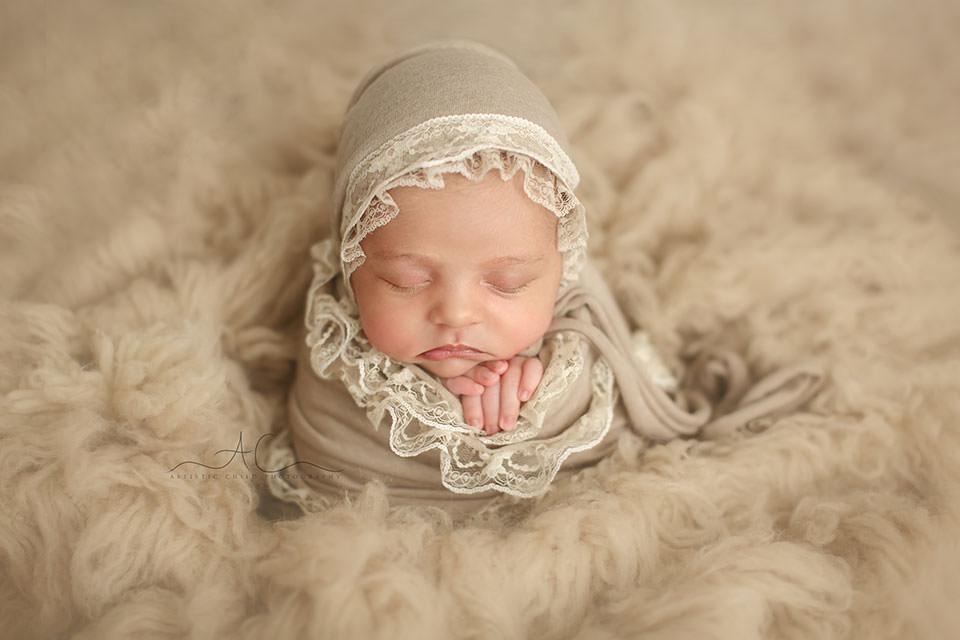 newborn baby girl photographed on a beige flokati | London