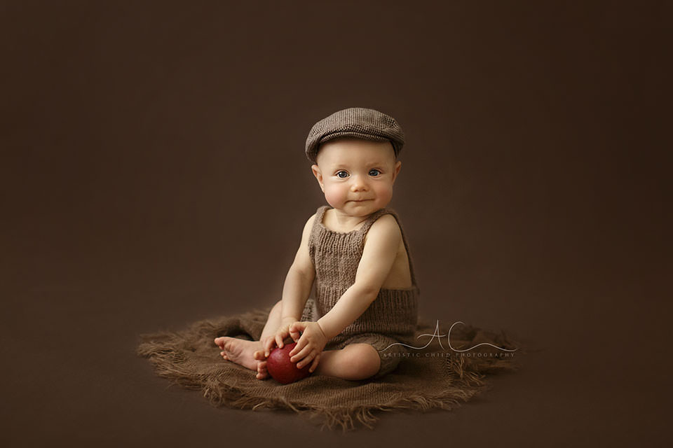 Bromley Baby Photography | 6 months old baby boy plays with a red apple during the professional photo session