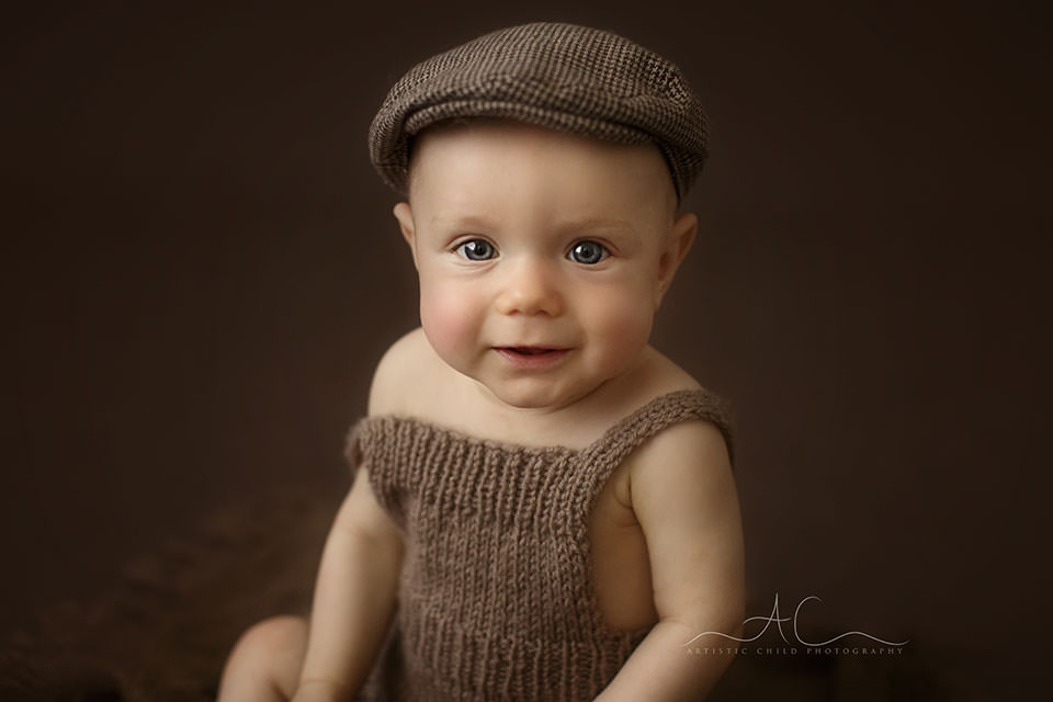 Bromley Baby Photography | close up portrait of a 6 months old baby boy in a brown flat cap