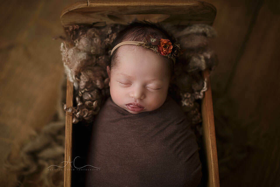 London Newborn Baby Girl Photography | photo of a newborn baby girl sleeping in a tiny wooden bed prop