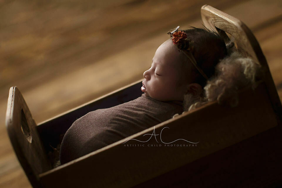 London Newborn Baby Girl Photography | a backlit portrait of a newborn baby girl sleeping in a tiny wooden bed