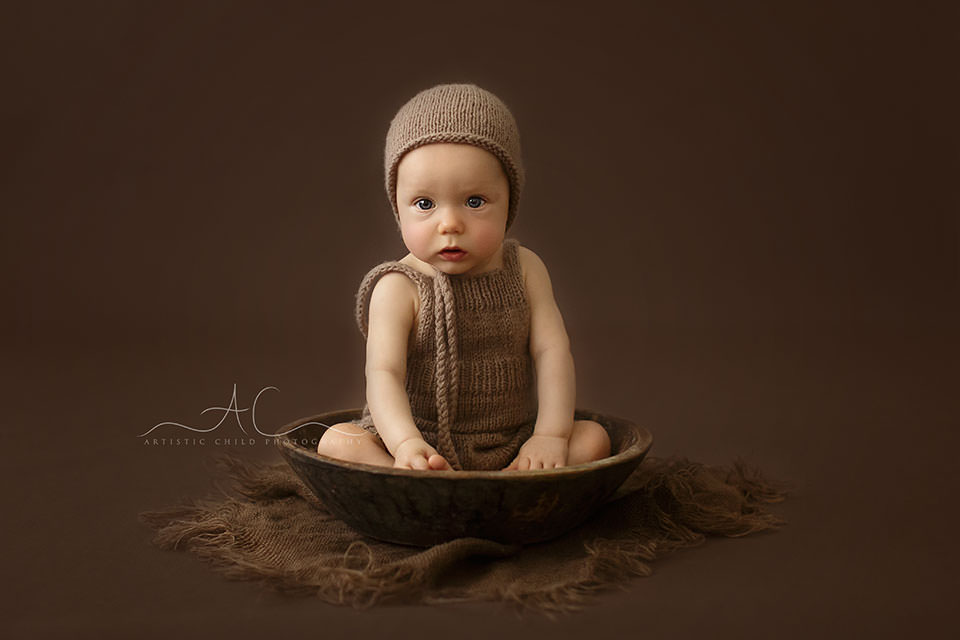 portrait of a 6 months old baby boy sitting in a wooden bowl | London