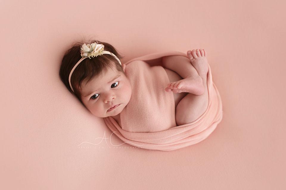Professional Bromley Newborn Photo Session | portrait of an awake newborn baby girl wearing a pretty flower headband