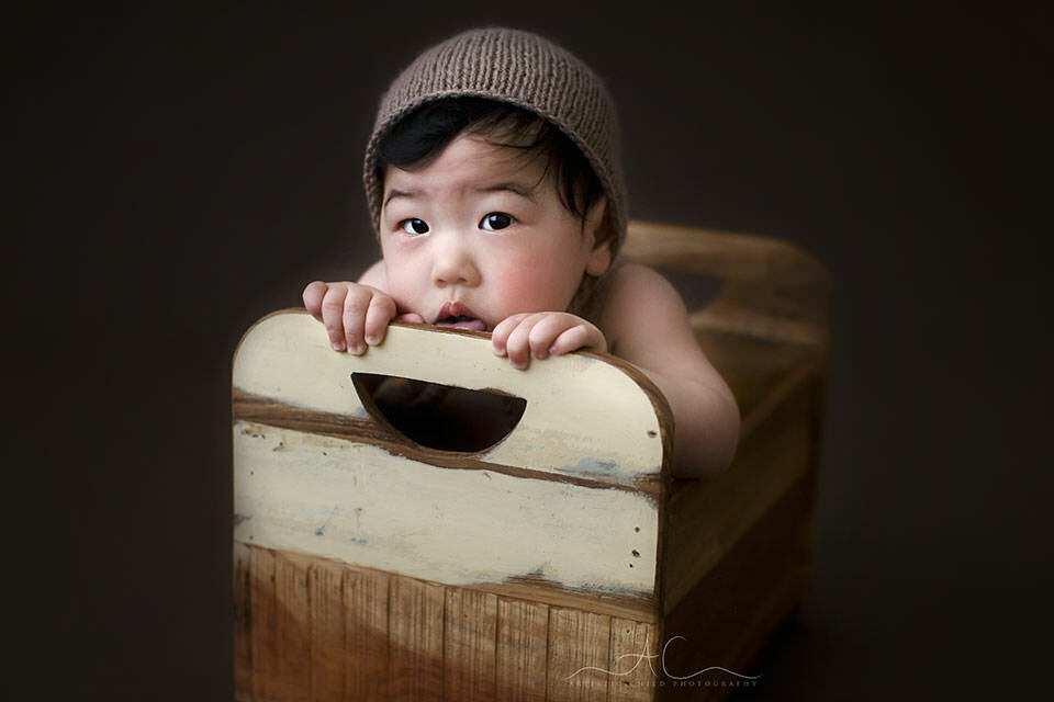Professional London Baby Boy Photos | baby boy photographed in a tiny wooden bed