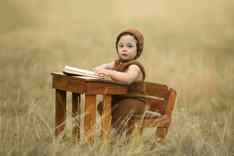 Professional South East London Toddler Photos | 1 year old toddler boy sits at the desk and reads a book in the park