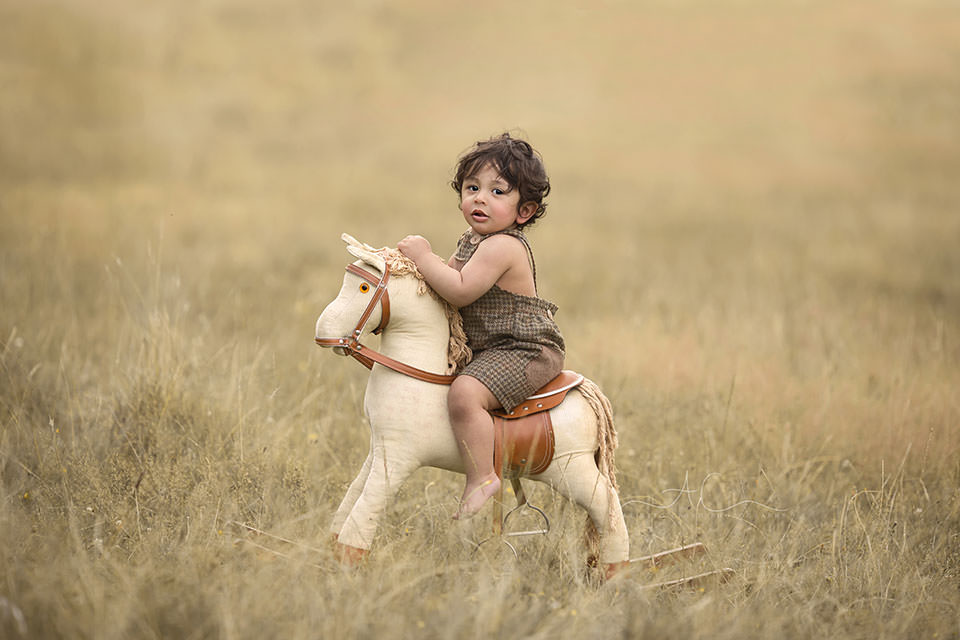 Professional South East London Toddler Photos | an outdoor portrait of a 1 year old toddler boy on a rocking horse