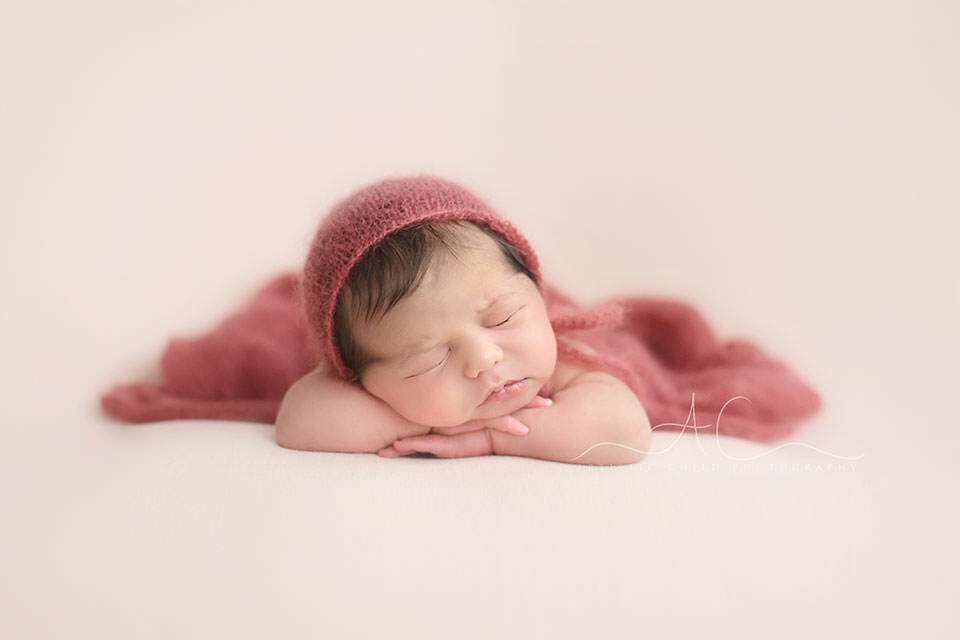 portrait of a newborn baby girl photographed in chin on hands pose | London
