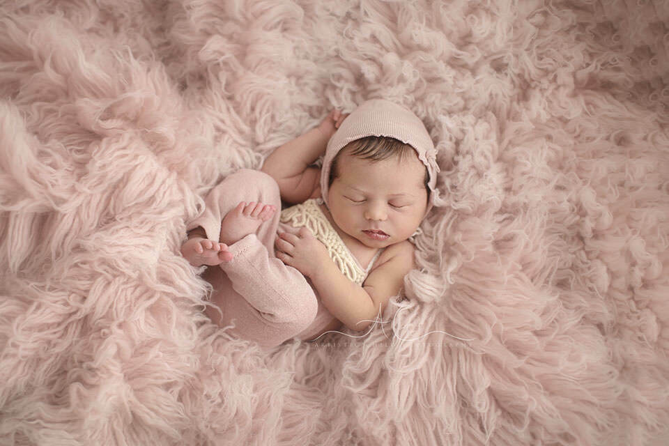 portrait of a newborn baby girl wearing pink pants and a hat while sleeping on a pink flokati | London
