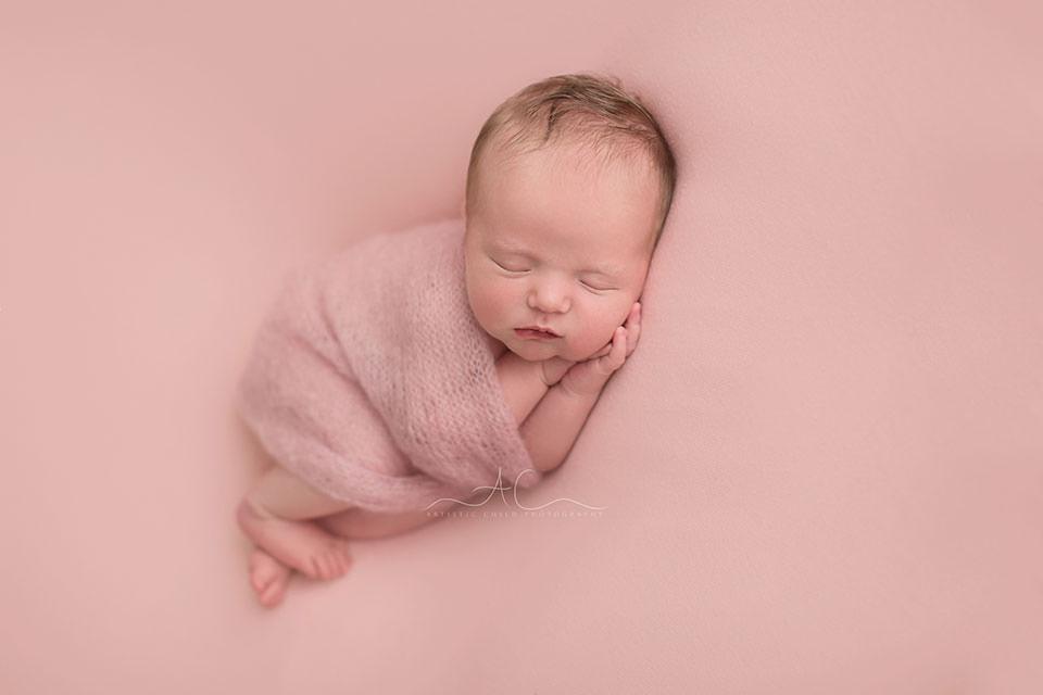 Bromley Newborn Baby Girl Photographer | portrait of a newborn baby girl sleeping on her side under a hand knitted pink blanket