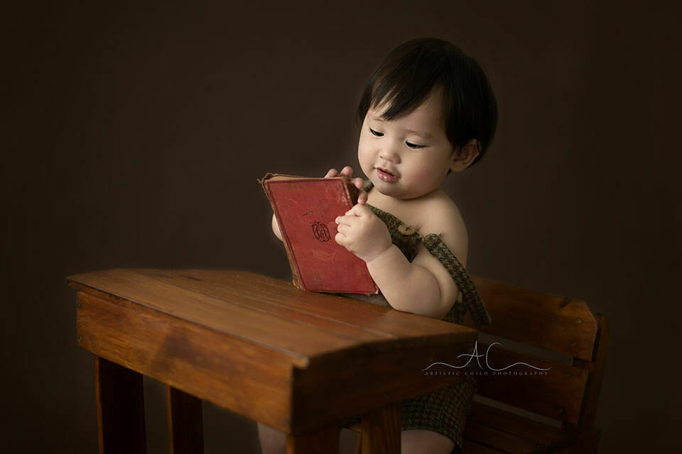 London Toddler Photography Offer | 1 year old toddler boy sits at the wooden desk and looks at the old red book