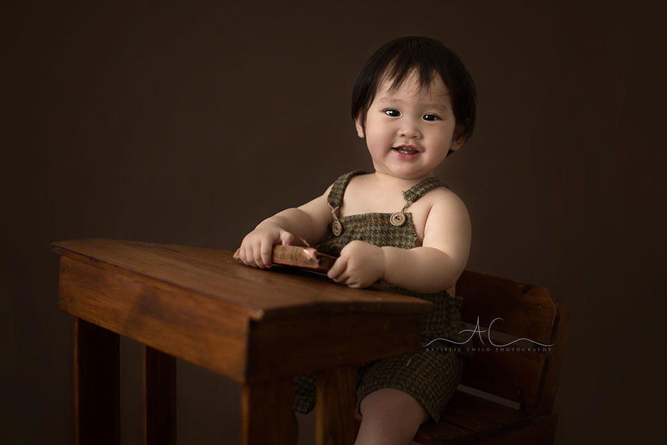 London Toddler Photography Offer | photo of a 1 year old toddler boy sitting at a wooden desk and smile during his first birthday photo session