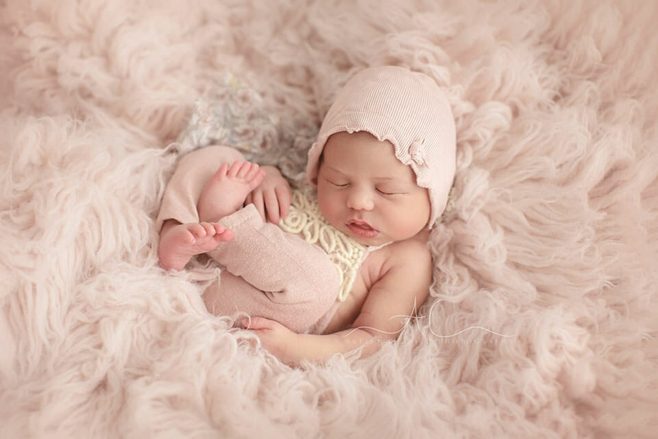 Professional Bromley Newborn Photography Services | newborn baby girl wears pink romper and a hat while photographed during her newborn photo session