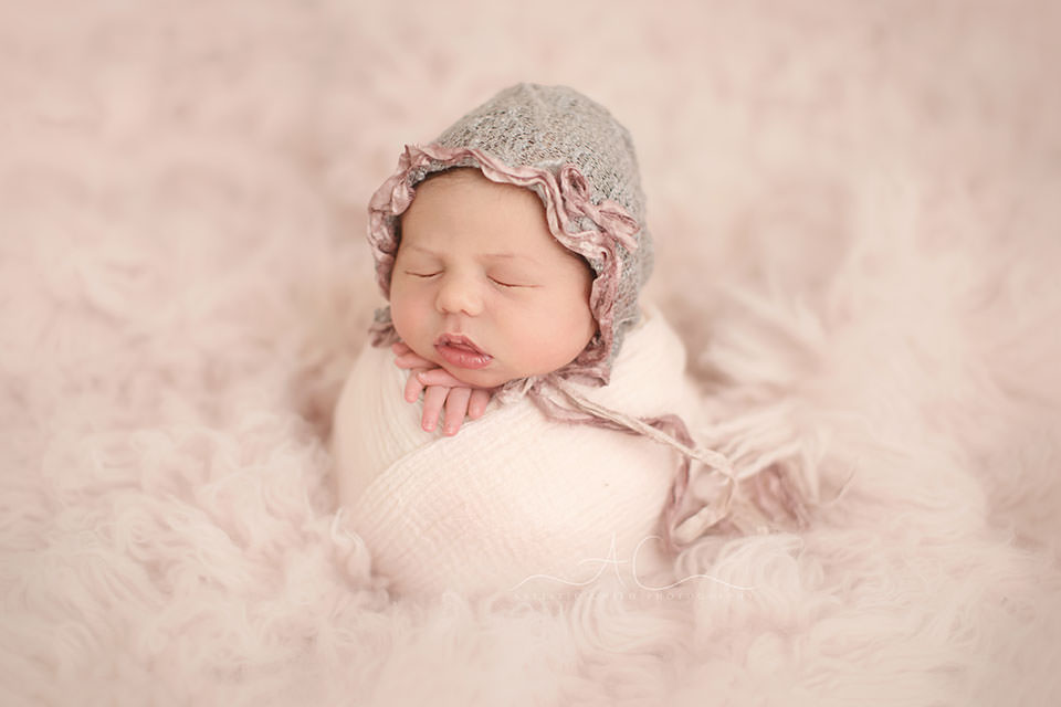 Professional Bromley Newborn Photography Services | photo of a newborn baby girl taken on a pink flokati