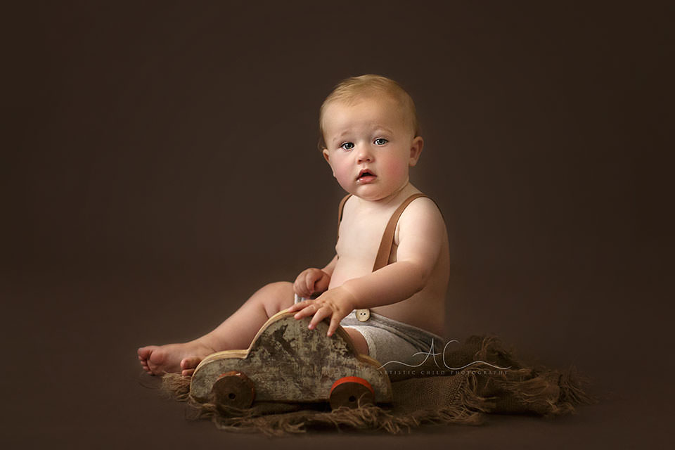 portrait of a 10 months old baby boy playing with a wooden car toy | London