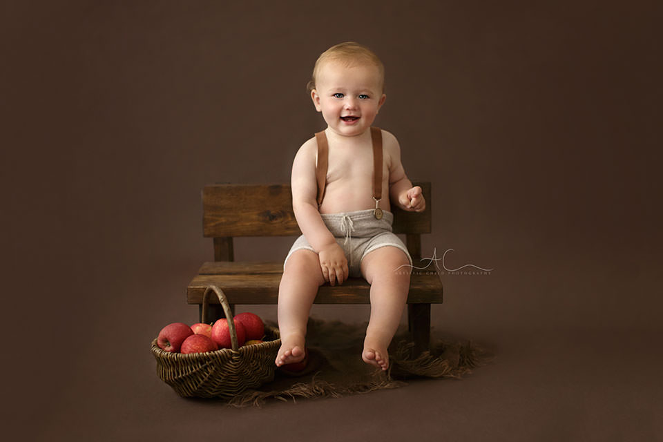 portrait of a 10 months old baby boy sitting on a small wooden bench with a wicker basket full of red apples next to it | London