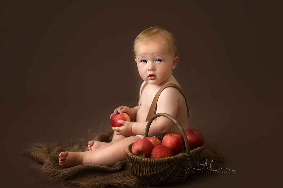 South East London Baby Boy Photos | portrait of a 10 months old baby boy playing with a basket full of red apples