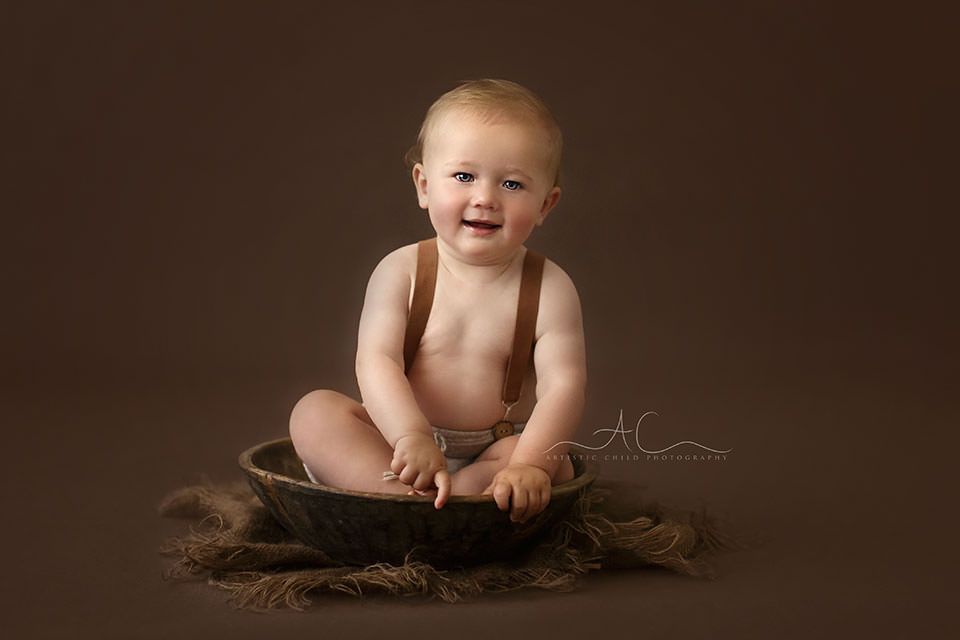 South East London Baby Boy Photos | 10 months old baby boy sits in a wooden bowl