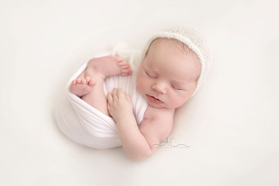 Studio London Newborn Photography | photo of a newborn baby boy wearing a white hand knitted hat