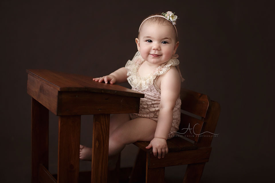8 months old baby girl plays at wooden desk prop during a professional photo session   London