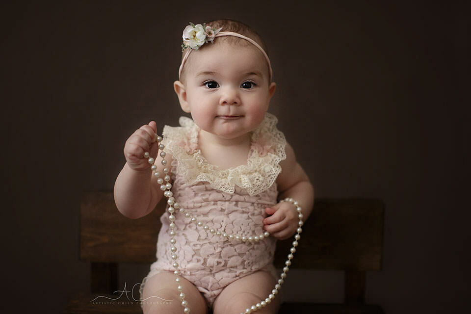Bromley Baby Photography Offer | 8 months old baby girl plays with a pearl neckles