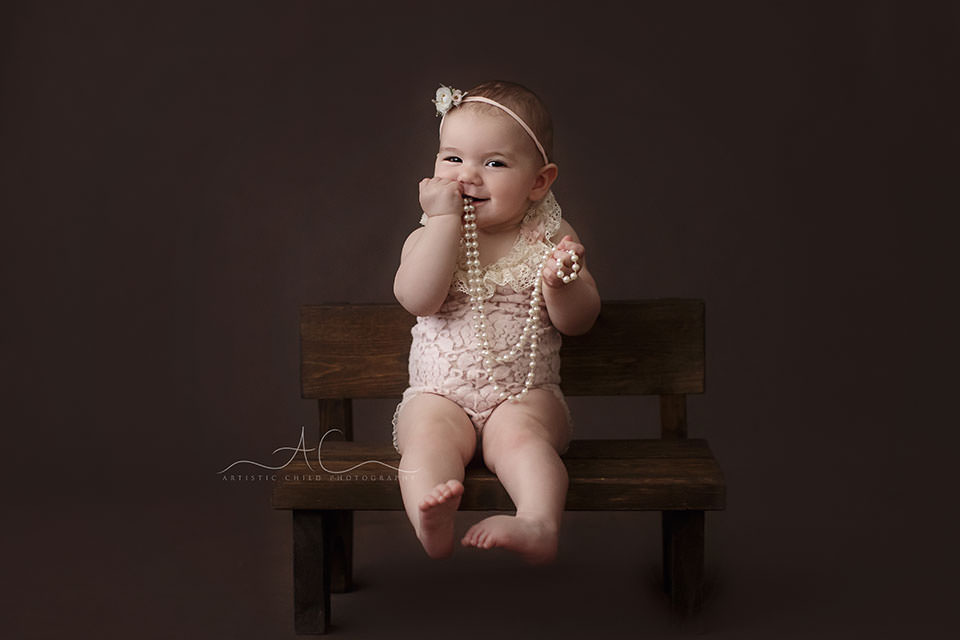 Bromley Baby Photography Offer   8 months old baby girl sits on a small wooden bench and plays with pearl neckles