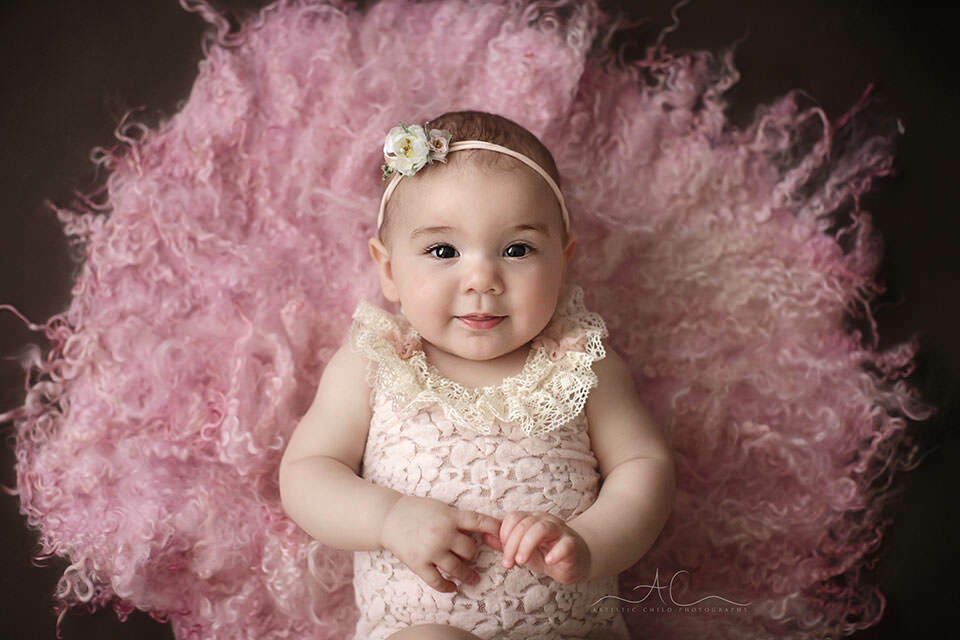 Bromley Baby Photography Offer   portrait of 8 months old baby girl wearing a pink flower tieback