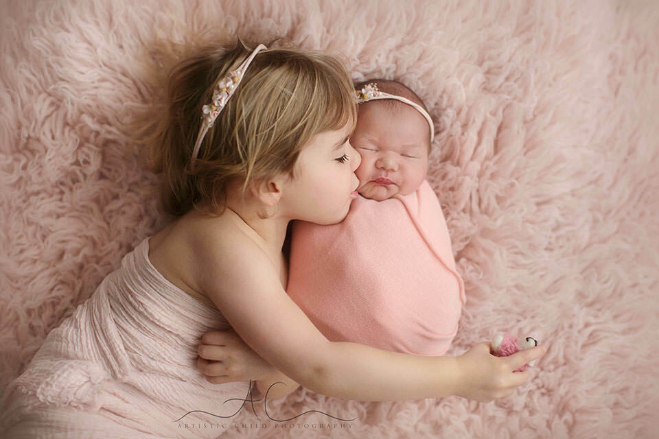 London Sibling Pictures | 3 year old older sister kisses her newborn sister in the cheek