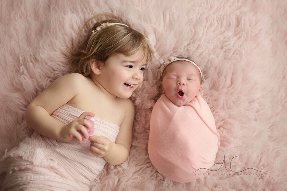 a sibling portrait of a newborn baby girl yawing and her older sister looking at her | London