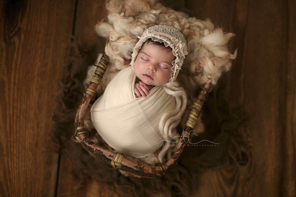 swaddled newborn baby girl sleeps in a bamboo basket during her first professional photo session | London