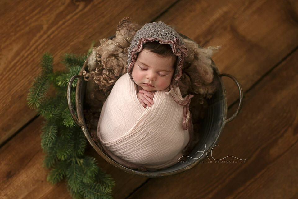 newborn baby girl sleeps in a metal backet during the professional photo session   London