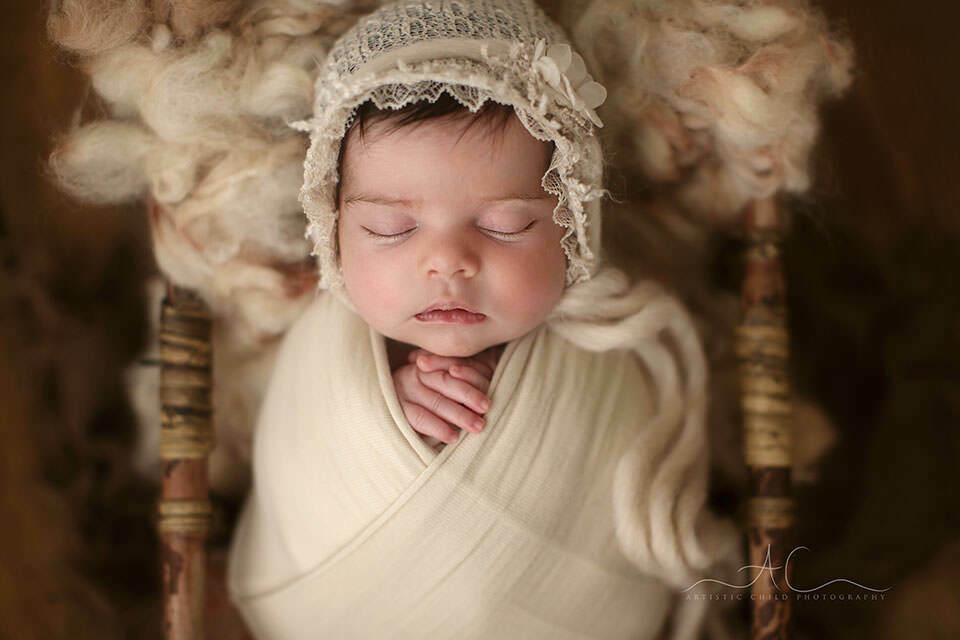South East London Newborn baby Girl Photography Services | a close up portrait of a newborn baby girl wearing a pretty lace bonnet