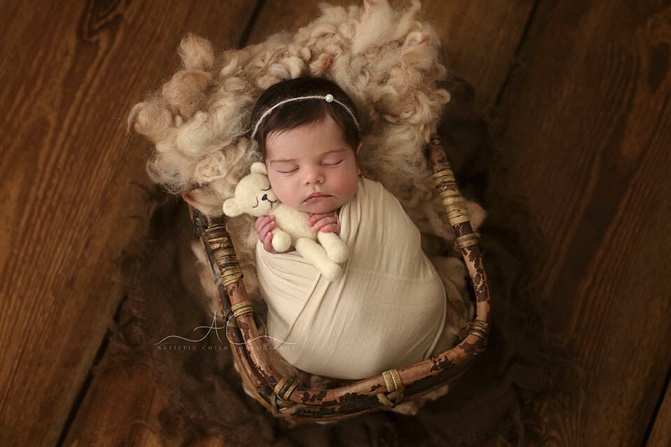 South East London Newborn baby Girl Photography Services   newborn baby girl holds a white teddy bear while sleeping in a bamboo basket