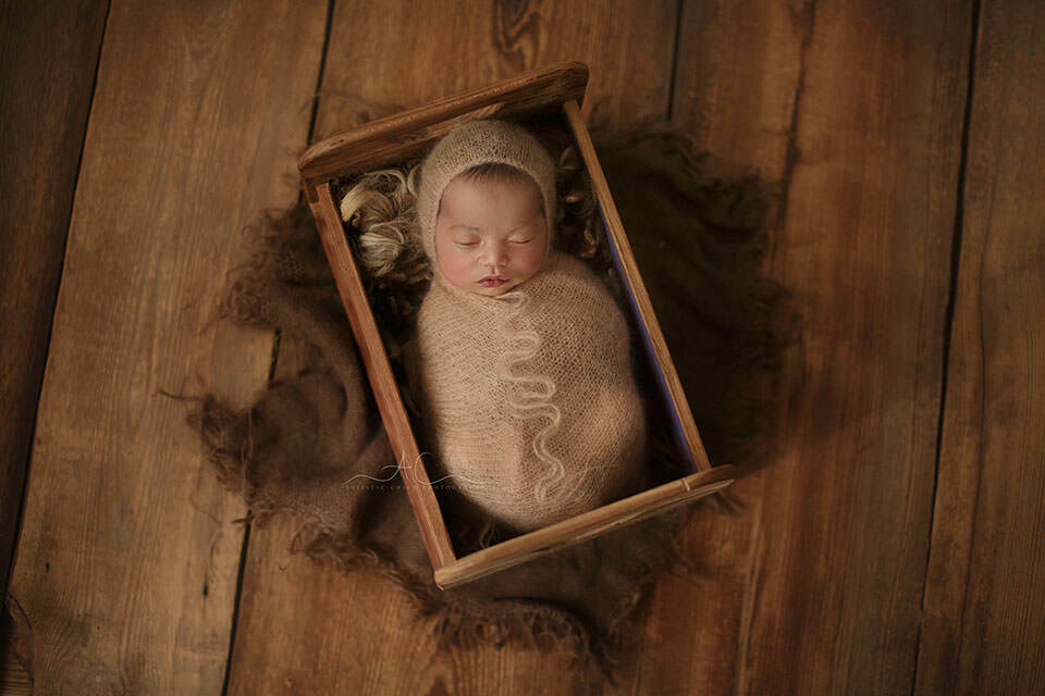 newborn baby boy sleeps in a tiny wooden bed prop during his newborn photo session | London