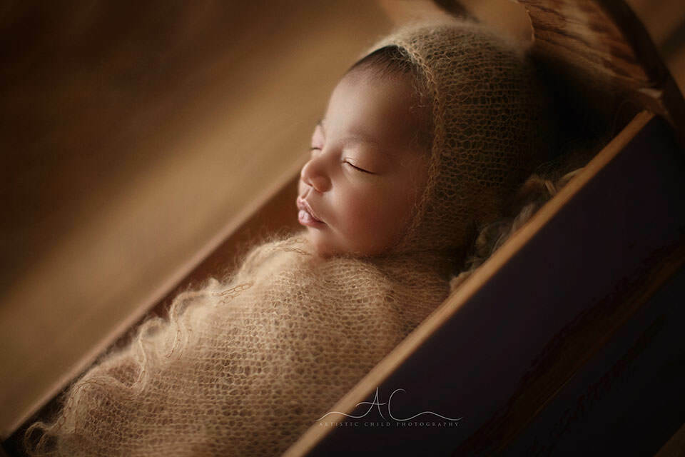a backlit portrait of a newborn baby boy sleeping in a tiny wooden bed prop | London