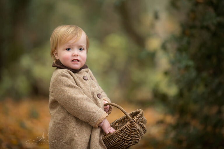 Bromley Toddler Portraits   18 months old girl carries a wicker basket in the park during autumn season