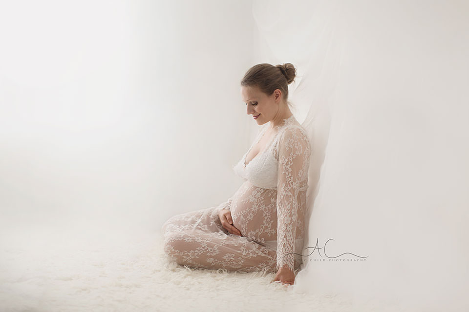 London Pregnancy Pictures | maternity portrait of a pregnant woman looking her her bump and smiling gently