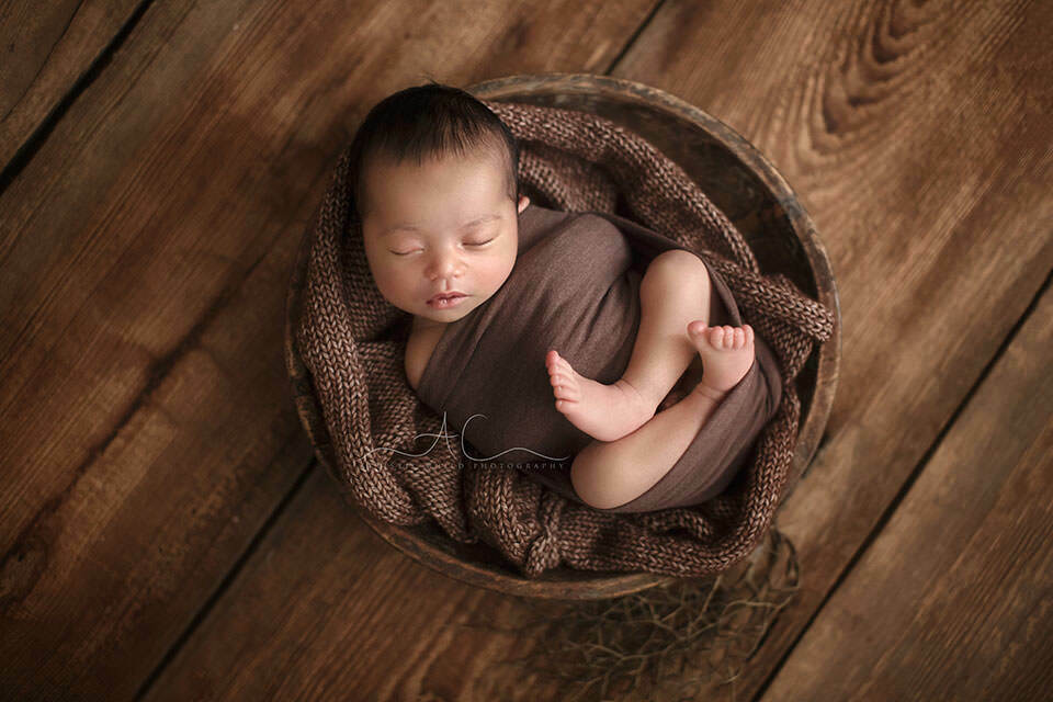 South East London Newborn Baby Boy Photo Session | newborn baby boy sleeps in a rustic wooden bowl